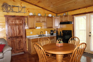 photo of the inside of a Kentucky log cabin. A vacation rental close to Lake Cumberland. Photo is taken of the kitchen and eating area of the log cabin.