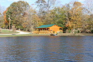 Photo of a log cabin with a beautiful pond in the foreground. Kentucky log cabin rental close to Lake Cumberland