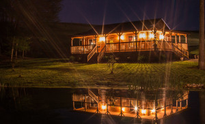 Photo of a Kentucky log cabin at night with the porch lights reflecting in the pond. Night time log cabin rental in Kentucky