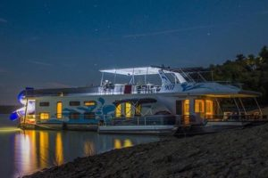 Photo of a beautiful Lake Cumberland houseboat with lights on at night on the lake in a Lake Cumberland cove.
