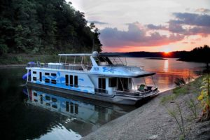 Photo of a Lake Cumberland State Dock rental houseboat in a Lake Cumberland cove with a beautiful sunset behind the houseboat