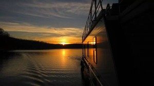 Photo of a houseboat on Lake Cumberland at night with a sunset in the horizon