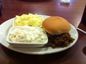 photo of a BBQ sandwich with cole slaw and potato salad on a plate