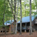 photo of two authentic modern Kentucky log cabins.  One cabin is made of grey logs and the other log cabin has light wood logs.  Both Kentucky log cabin rentals have blue roofs