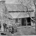photo of a family outside their log cabin around the year 1800.  Black and white early log cabin photograph. Kentucky.