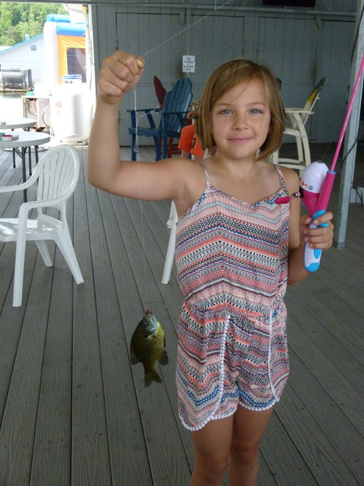 Photo of a little girl holding a fish at the Lake Cumberland State Dock Marina Kids Day Celebration