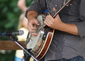 Photo of a banjo and a man playing at the Lake Cumberland Bluegrass Festival