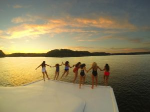 Photo of girls jumping off the top of a houseboat on Lake Cumberland in Jamestown, Kentucky