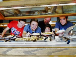 Photo of a beautiful buffet dinner at Lake Cumberland State Resort Park and a family holding plates of delicious foods