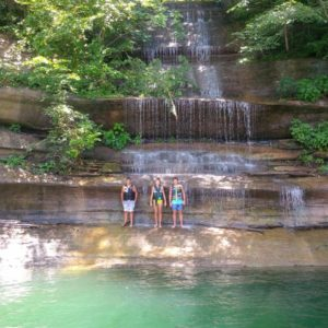 Photo of 3 kids standing under a Lake Cumberland Waterfall